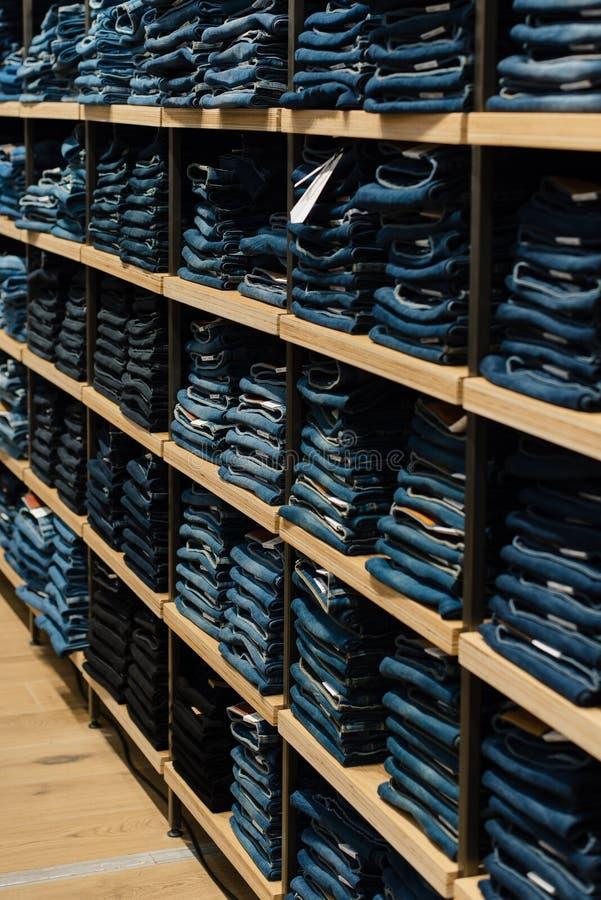 Куча джинсов на окне магазина в магазине Сложенные джинсы на полке стоковая фотография