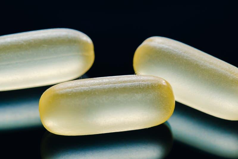 Куча желтых пилюлек капсулы tablets лежать медицины изолированных на черном конце-вверх крайности предпосылки стоковые фотографии rf