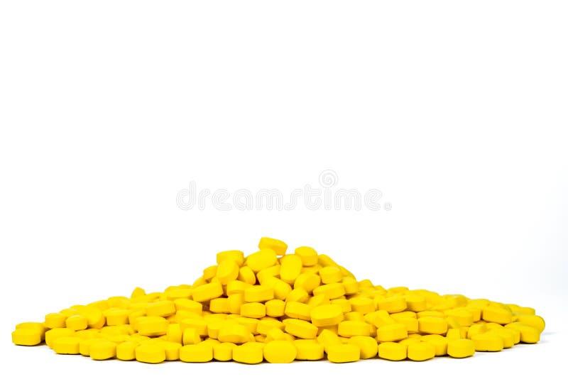 Куча желтых ovoid-прямоугольных пилюлек таблетки формы изолированных на белой предпосылке с космосом экземпляра медицина для боли стоковая фотография rf