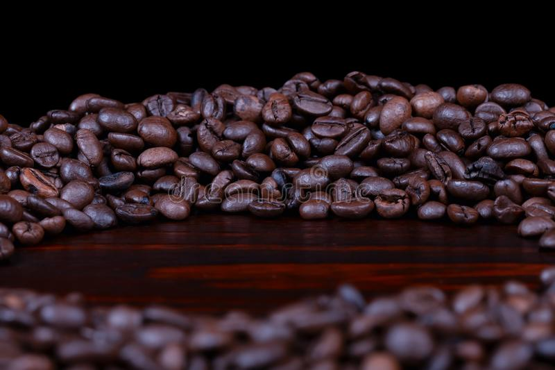 Куча зажаренных в духовке кофейных зерен сложила в круге на mahogany изолированной древесине стоковые фото