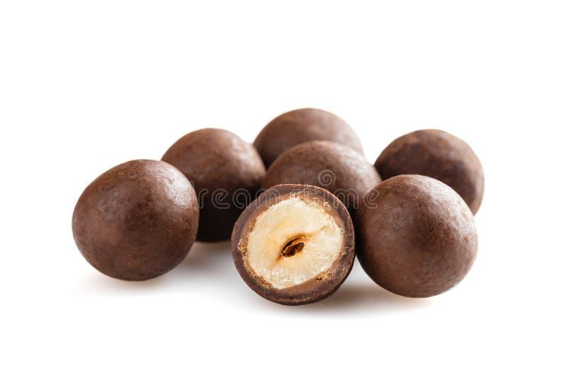 Куча засахаренных dragees фундуков в шоколаде изолированном на белизне стоковая фотография