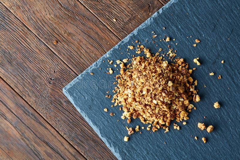 Куча здорового granola на черной каменистой доске над винтажной деревянной предпосылкой, взгляд сверху, концом-вверх, селективным стоковые фото