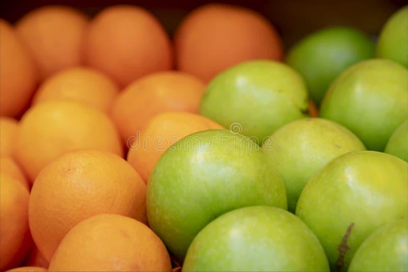 Куча зеленых зрелых яблок и апельсины закрывают вверх стоковые изображения rf
