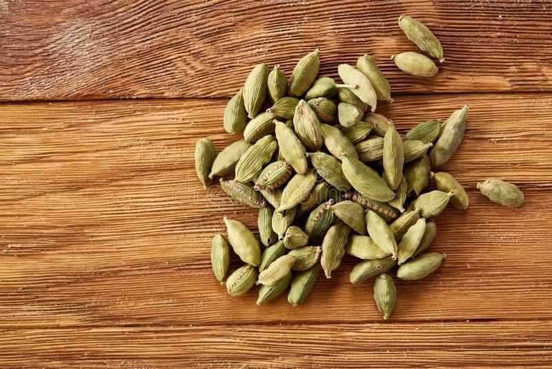 Куча зеленых семян cardamon на деревенском деревянном конце-вверх предпосылки, взгляд сверху, селективном фокусе стоковая фотография rf