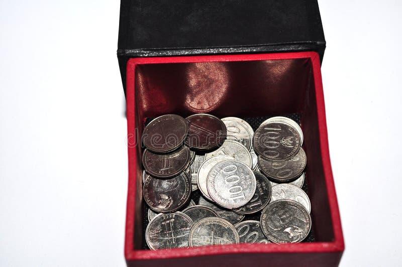 Куча индонезийской монетки в коробке изолированной на белой предпосылке стоковая фотография