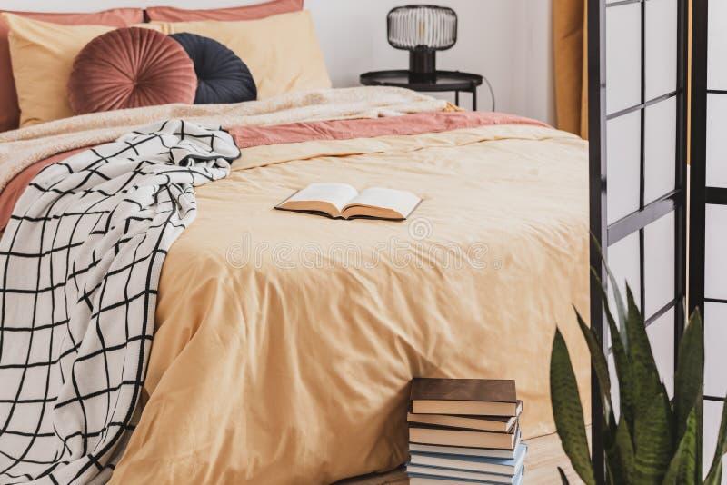 Куча книг в ноге королевской кровати с желтыми подушками одеяла и имбиря стоковые фото