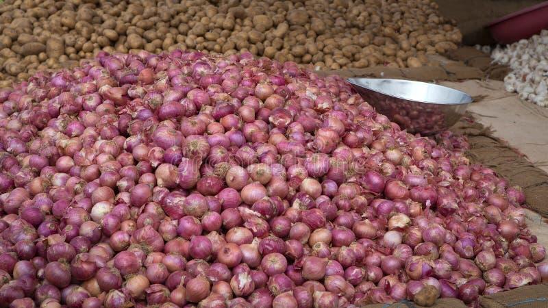 Куча красных луков и картошек на рынке овоща стоковые изображения rf