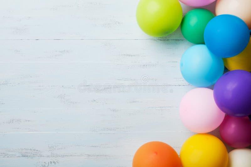 Куча красочных воздушных шаров на голубом взгляд сверху деревянного стола прикрепленная карточка коробки дня рождения предпосылки