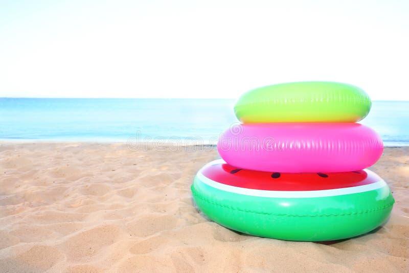 Куча красочных раздувных колец на песке стоковые фото