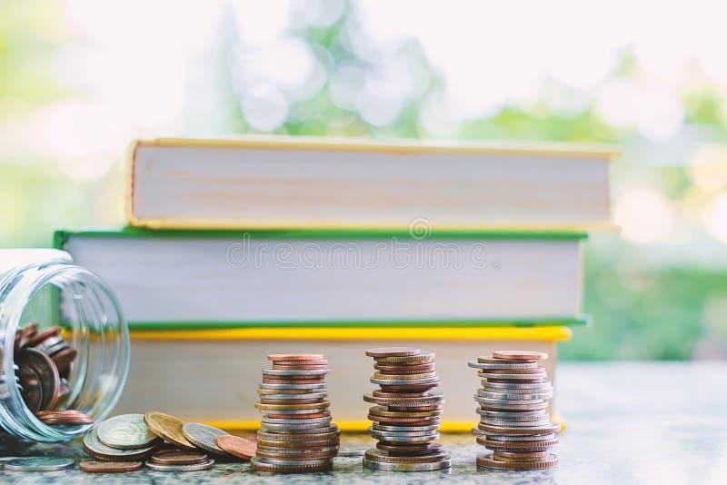 Куча монеток денег вне стеклянного опарника перед книгами на b стоковое изображение rf