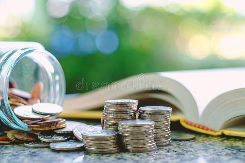 Куча монеток денег в и снаружи стеклянного опарника на запачканной книге стоковая фотография