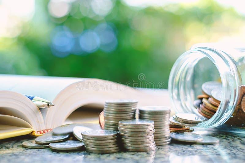 Куча монеток денег в и снаружи стеклянного опарника с книгой o стоковое фото rf