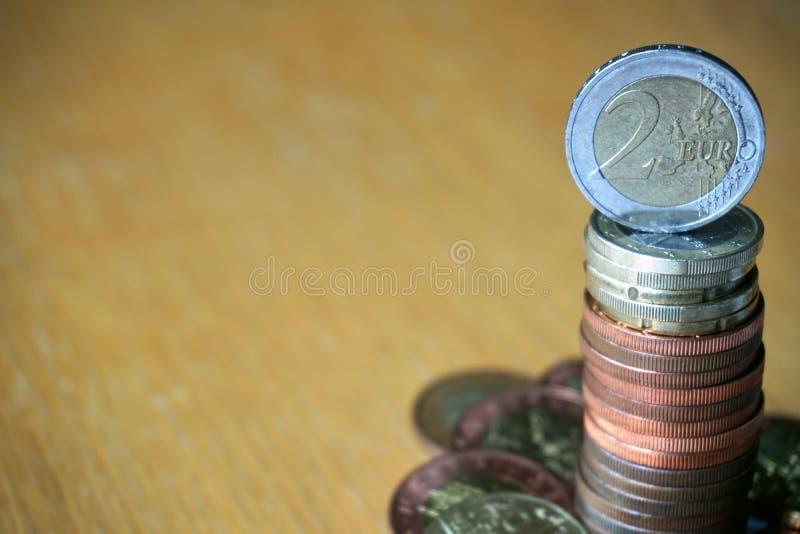 Куча монеток на деревянном столе с золотой монеткой евро на верхней части стоковая фотография rf
