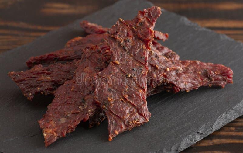 Куча отрывистого говядины черного перца на деревенском деревянном столе стоковое фото