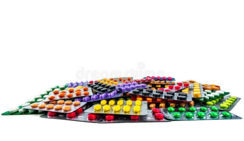 Куча пилюлек таблетки изолированных на белой предпосылке Желтые, фиолетовые, черные, оранжевые, розовые, зеленые пилюльки таблетк стоковое изображение