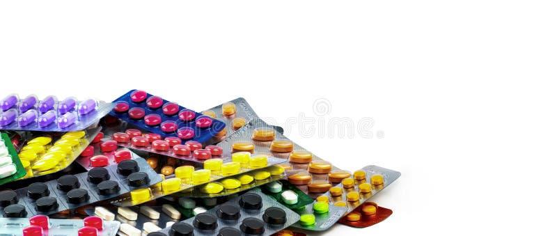 Куча пилюлек таблетки изолированных на белой предпосылке Желтые, фиолетовые, черные, оранжевые, розовые, зеленые пилюльки таблетк стоковые изображения rf
