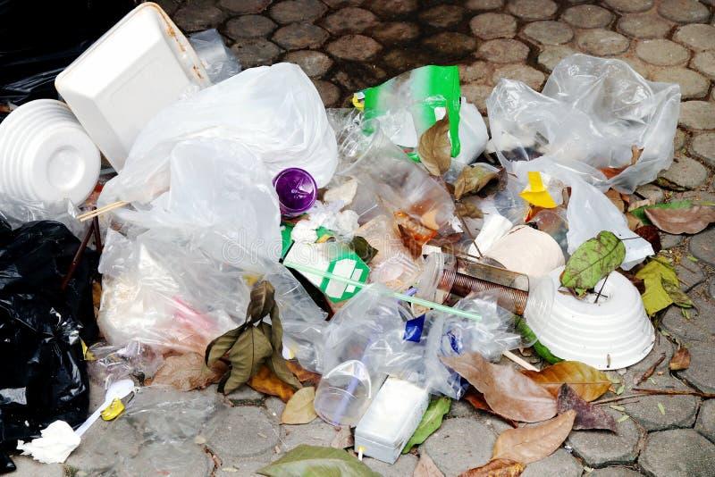 Куча пластичного отброса на поле, стекле отхода пластмассы отброса и соломах, отходе полиэтиленового пакета, отходе еды подноса п стоковое фото rf