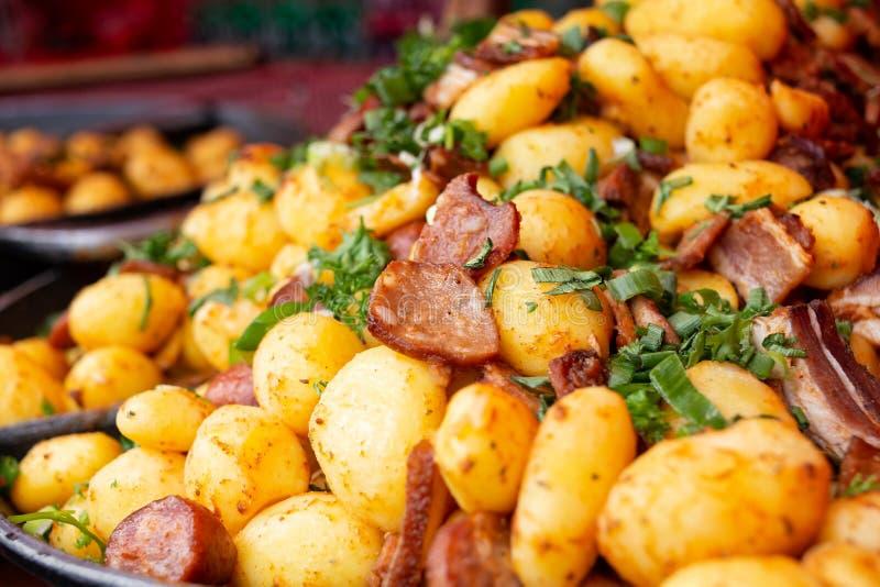 Куча сваренных картошек смешала с зажаренными европейскими сосиской и петрушкой Еда улицы стоковые фото