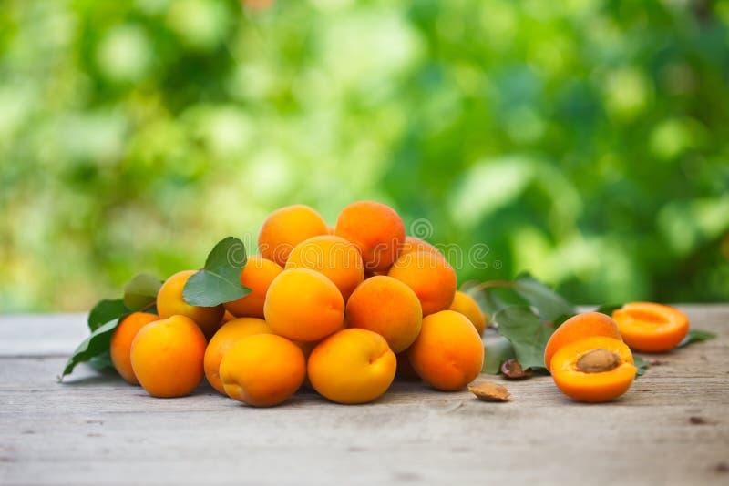 Куча свежих абрикосов с листьями aprcicot на старом деревянном столе стоковые фото
