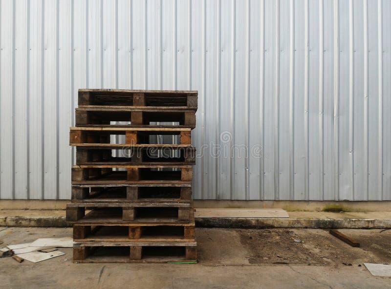 Куча старого деревянного паллета на пакостной земле перед стальной стеной в индустрии стоковая фотография rf