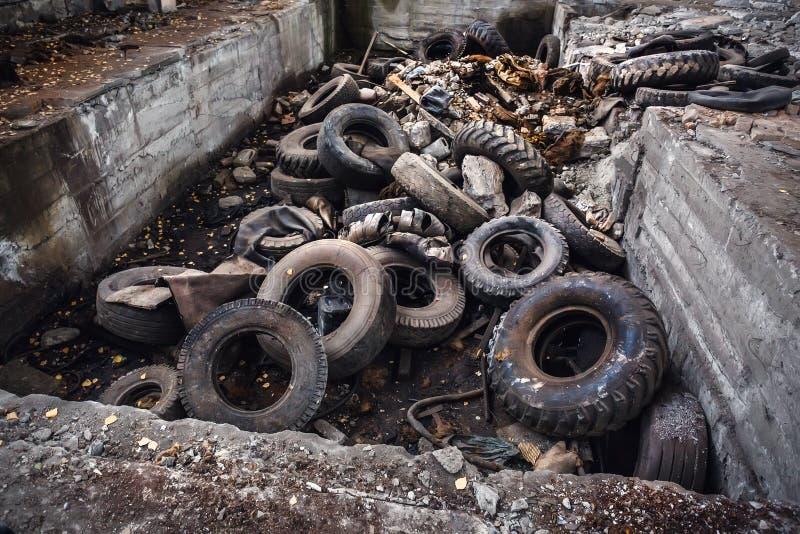 Куча старых автошин старья автомобиля, используемых колес хлама тележки, промышленного отброса в покинутой фабрике стоковая фотография rf