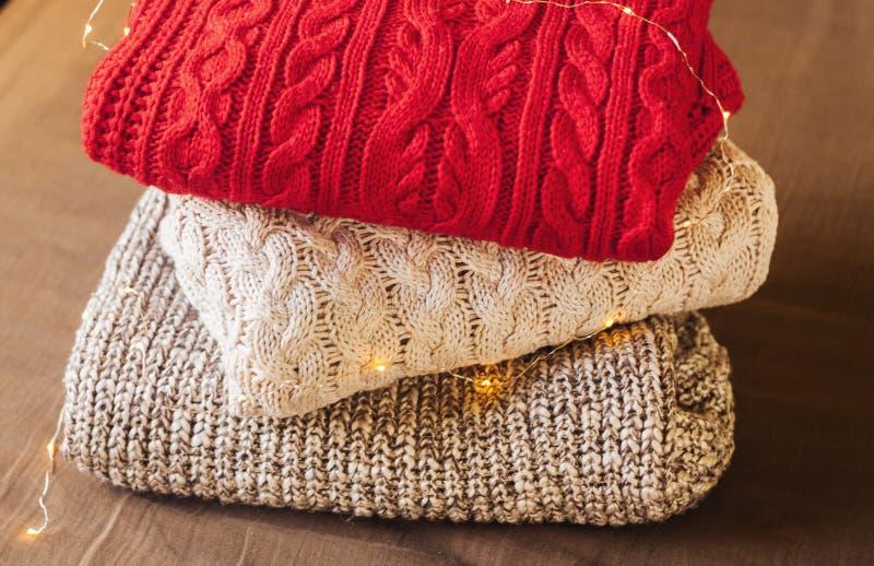 Куча теплых свитеров на предпосылке ткани украшенной со светами стоковое изображение