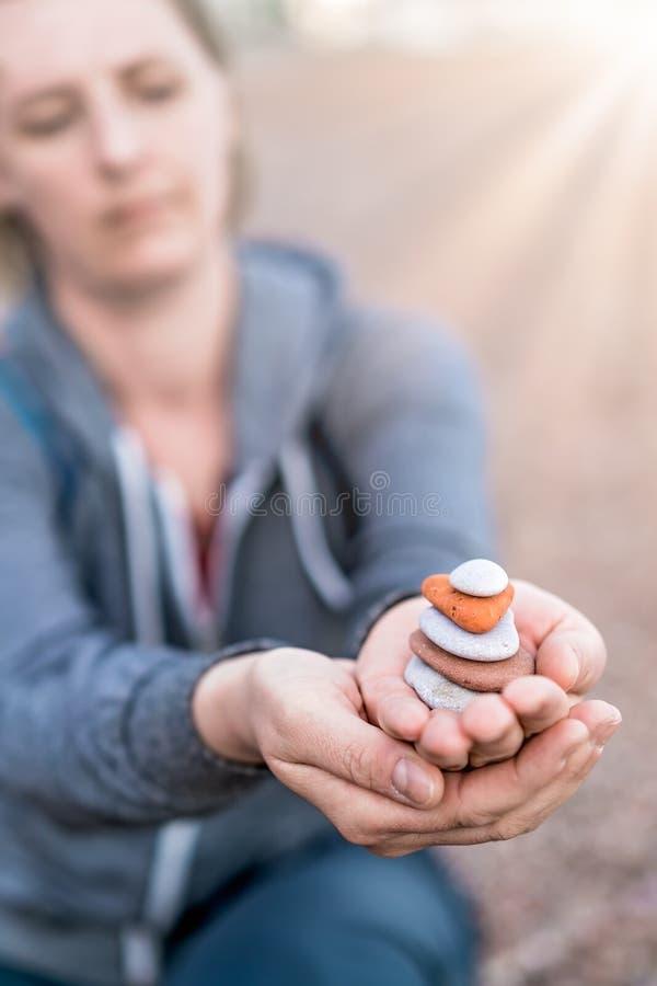Куча удерживания женщины камней стоковое изображение