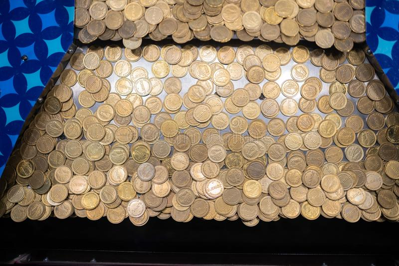 Кучи монеток в машине аркады стоковая фотография