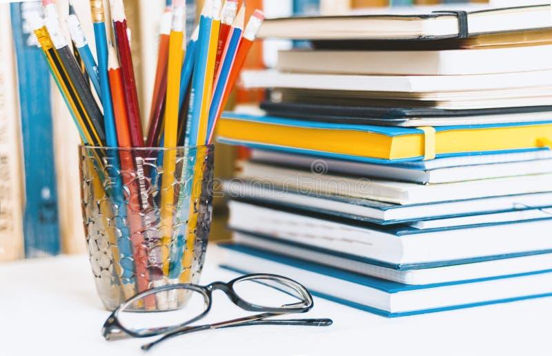 Кучи тетрадей, стог задней части образования книг к предпосылке школы, учебники, стекла и карандаши в пластиковом держателе с экз стоковые изображения