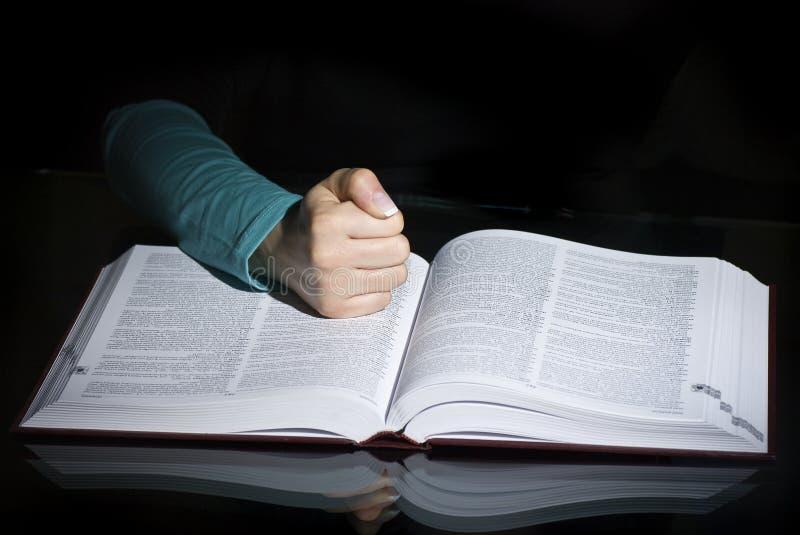 Кулак над открытой книгой стоковые изображения