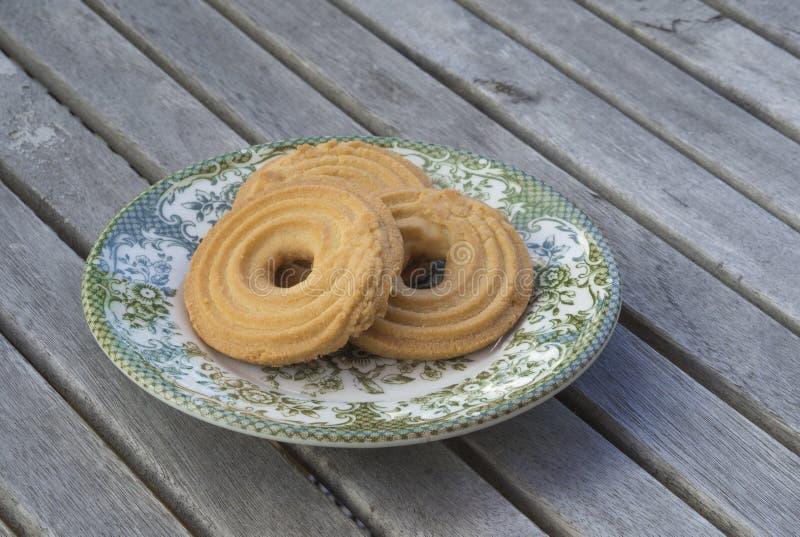 Кудрявые печенья печений масла на зеленом цвете покрасили плиту на деревянном стоковые фото