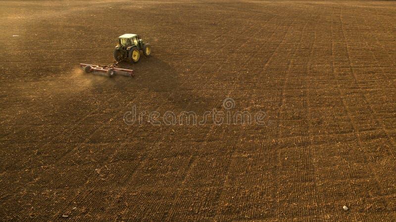 Культивировать трактора и мучительное поле стоковая фотография