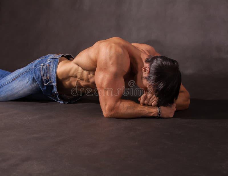 Культурист лежа на поле в студии стоковое фото