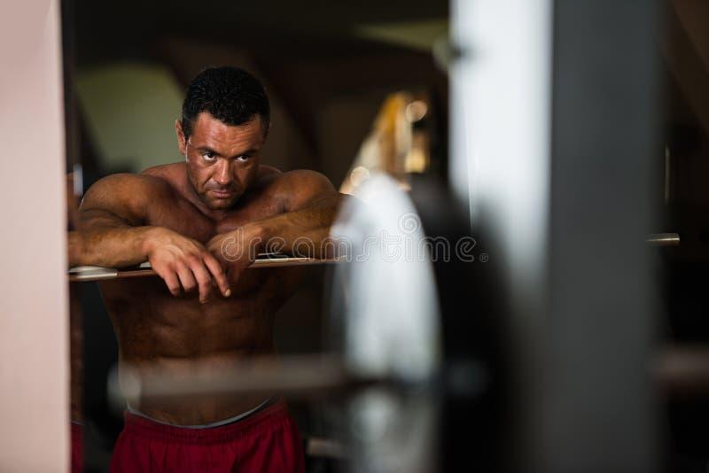 Культурист отдыхая после делать тяжеловесную тренировку стоковое изображение