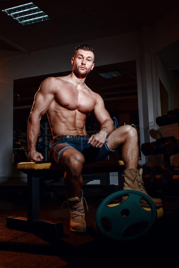 Культурист сидит на стенде веса, он принимает пролом Мышечный человек на месте разминки в спортзале и усмехаться к камере стоковые фотографии rf