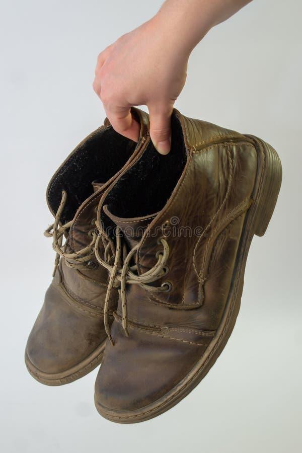 к妇女的手举行与蔑视老人的nubuck鞋子,摇晃鞋带 库存照片