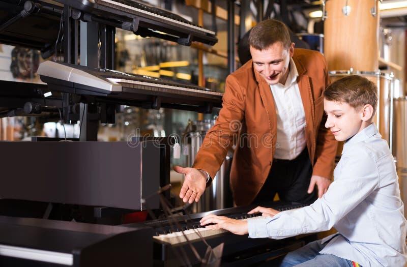 Клавиатуры отца и сын-подростка рассматривая в магазине гитары стоковое изображение rf