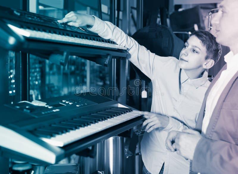 Клавиатуры отца и сын-подростка рассматривая в магазине гитары стоковое фото