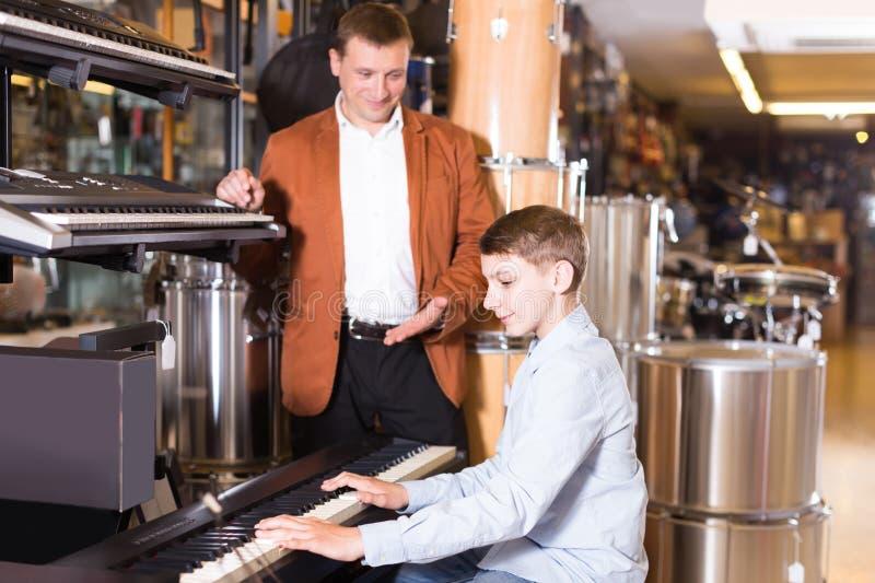 Клавиатуры отца и сын-подростка рассматривая в магазине гитары стоковое фото rf