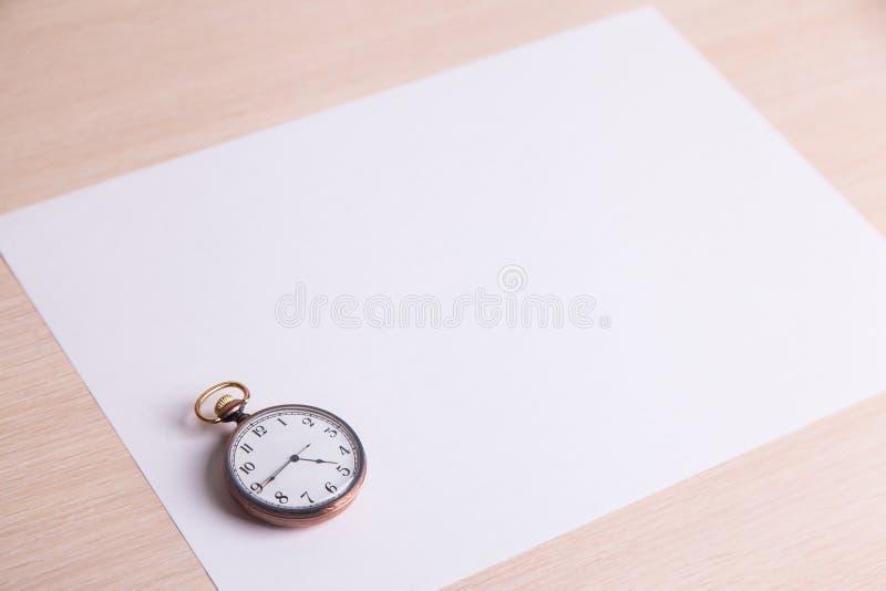 Классические часы на белом листе бумаги стоковые изображения