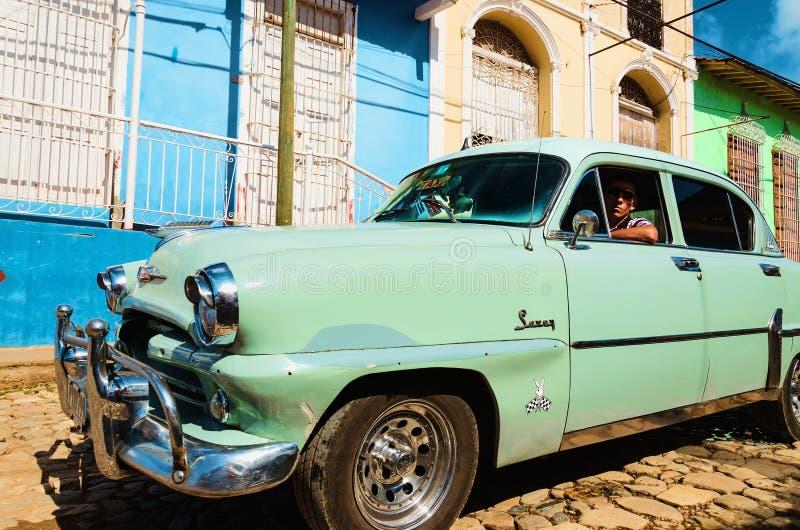 Классический американский автомобиль курсируя на колониальных улицах с красочными домами в Trinidiad, где старые автомобили стоковая фотография rf