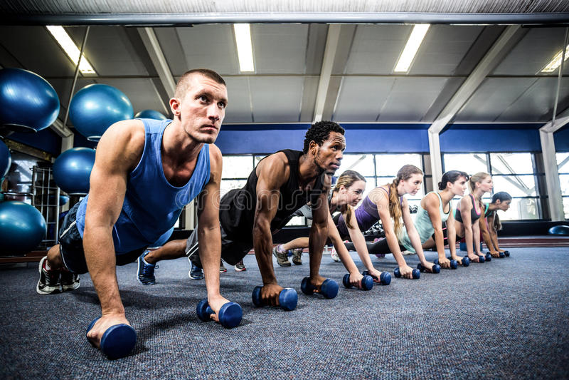 Класс фитнеса в положении планки с гантелями стоковые фото
