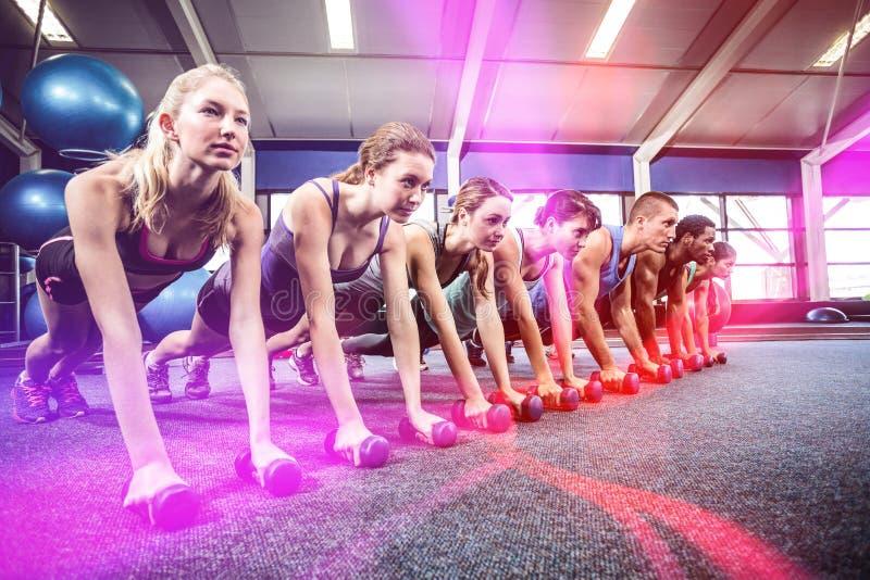 Класс фитнеса в положении планки с гантелями стоковое изображение rf