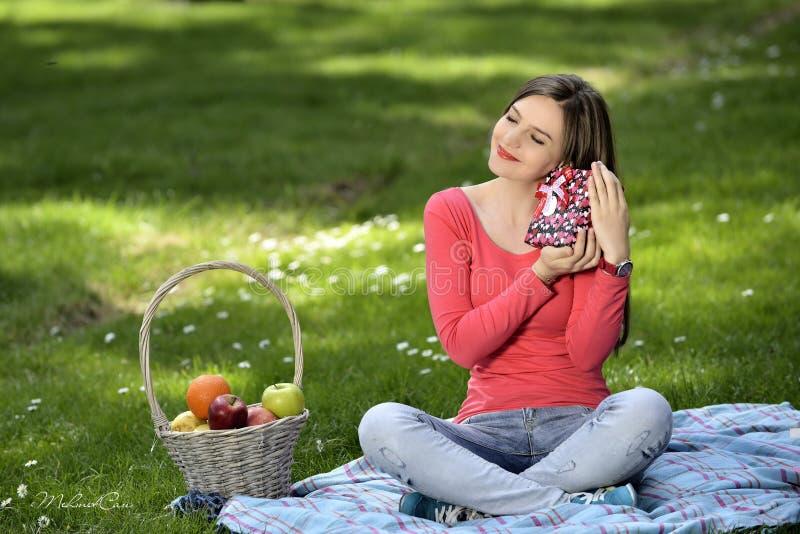 кладет детенышей в коробку женщины подарка счастливых стоковые изображения