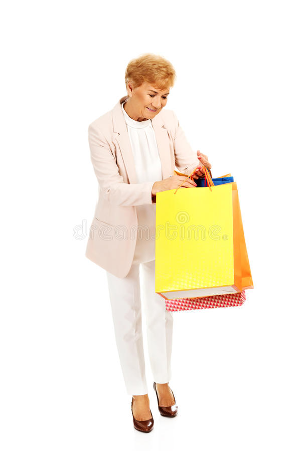 кладет женщину в мешки покупкы удерживания дела счастливую стоковое изображение rf