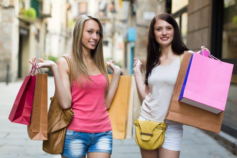 кладет ходить по магазинам в мешки девушок стоковые изображения