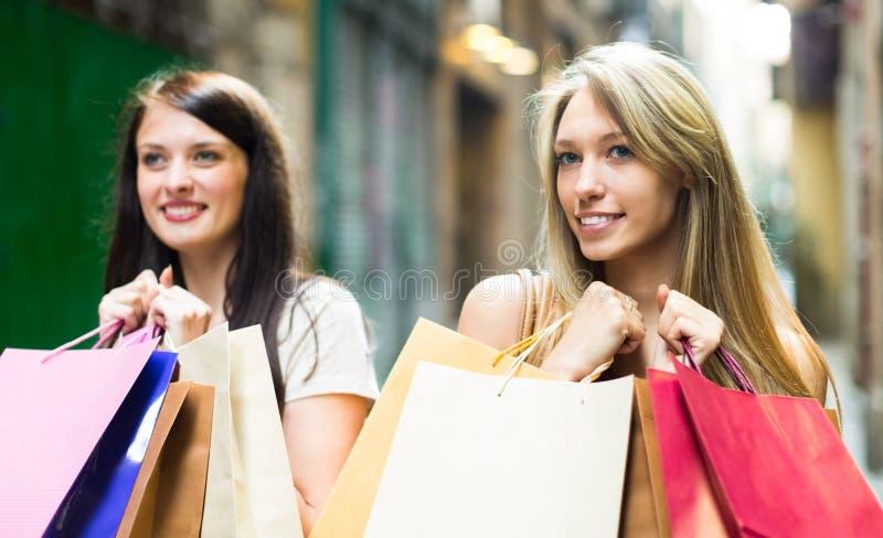 кладет ходить по магазинам в мешки девушок стоковые фото