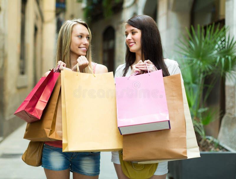 кладет ходить по магазинам в мешки девушок стоковое изображение rf