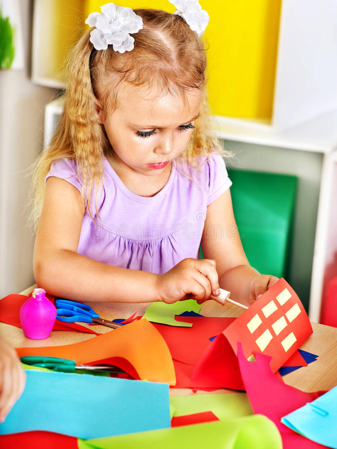 Клей девушки ребенка в preschool. стоковое фото rf