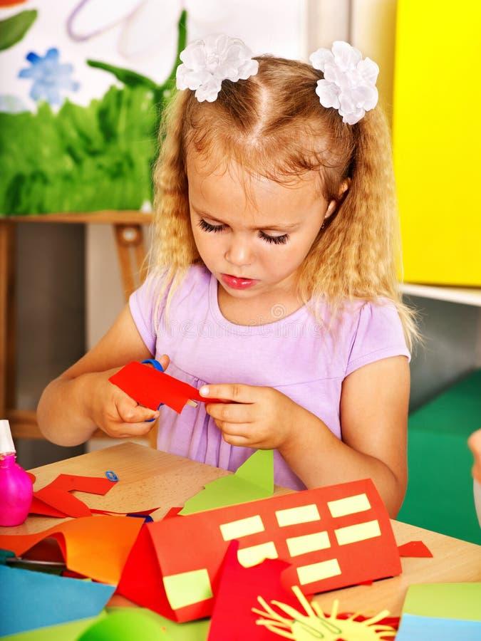 Клей девушки ребенка в preschool стоковое фото